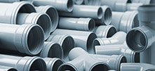 PVC plastic pipes and tubes stacked in warehouse.
